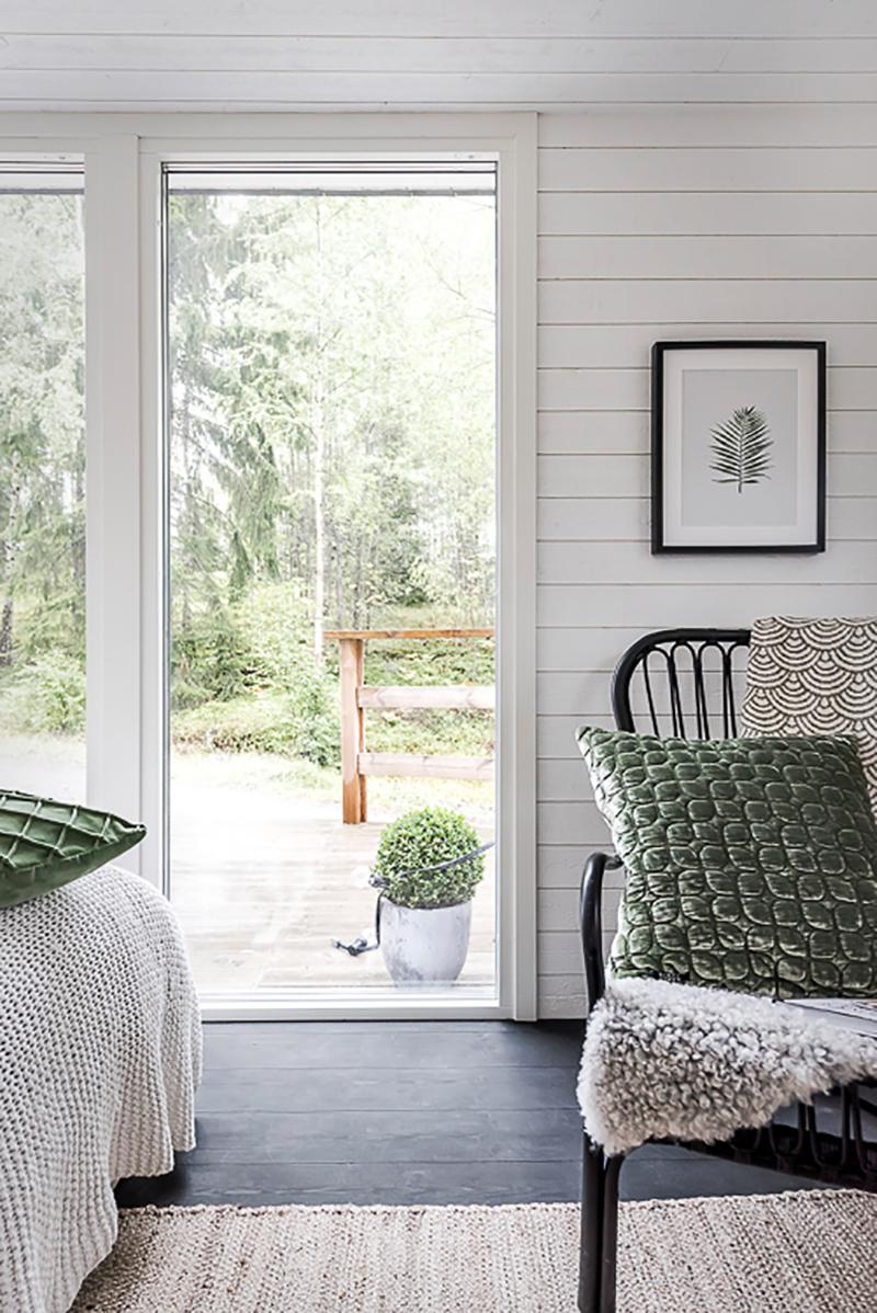 friggebod 15 kvm med vitmålad träpanel och svartvaxat golv