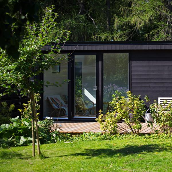 svart attefallhus i trädgård